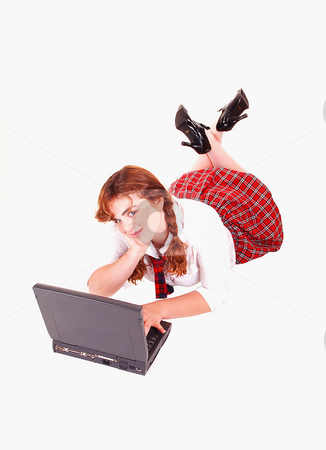 Schoolgirl with laptop. stock photo, A young red haired schoolgirl in her uniform lying on the floor with the laptop and thinking about her homework. by Horst Petzold
