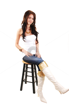 Pretty young girl. stock photo, Beautiful young girl in jeans and long white boots and jeans sitting on  a bar chair in the studio and smiling. by Horst Petzold