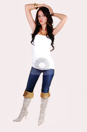 Slim girl standing. stock photo, A slim pretty girl in an white top, blue jeans and with boots with gold border and long black hair standing in the studio. by Horst Petzold