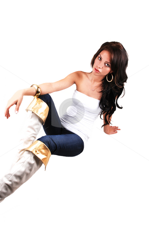 Slim girl sitting. stock photo, A slim pretty girl in an white top, blue jeans and with boots with gold border and long black hair sitting on the floor in the studio. by Horst Petzold