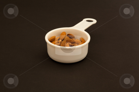 Cup of almonds stock photo, Almond is also the name of the edible and widely cultivated seed of this tree. Although popularly referred to as a nut, the almond seed or fruit is botanically not a true nut, but the seed of a drupe by Mariusz Jurgielewicz