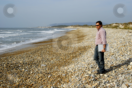 Beach stock photo, Young man at the beach with his laptop by Rui Vale de Sousa