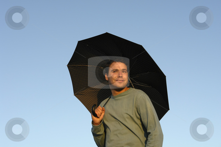 Umbrella stock photo, Young man with umbrella at sunset light by Rui Vale de Sousa