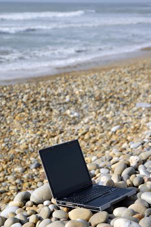 Laptop stock photo, Modern black laptop at the beach rocks by Rui Vale de Sousa