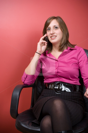 Business Woman At the Office stock photo, A young business woman talking on a cell phone while seated in her chair at work. by Todd Arena