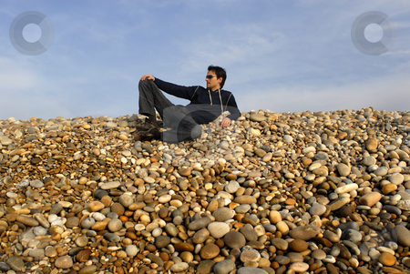 Beach stock photo, Young casual man at the beach stones by Rui Vale de Sousa