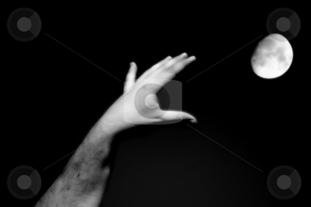 Hand reaching for the moon stock photo, Human hand trying to capture the moon by Rui Vale de Sousa