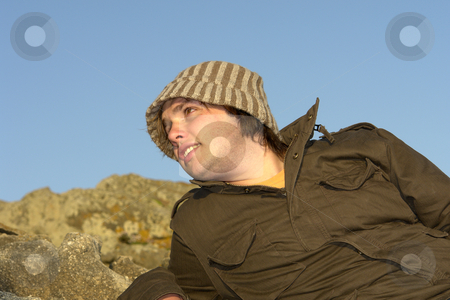 Laid stock photo, Young man at the rocky beach with a hat by Rui Vale de Sousa