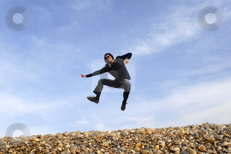 Jump stock photo, Young man jumps on beach, with the sky as background by Rui Vale de Sousa