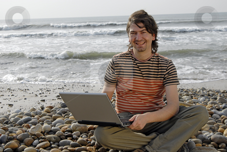 Working stock photo, Young man at the beach with laptop by Rui Vale de Sousa