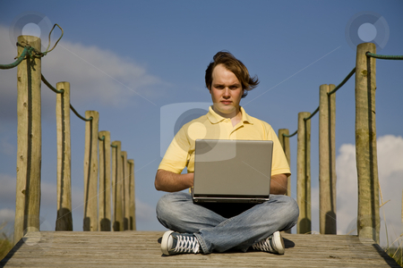 Working stock photo, Young man working with computer at the beach by Rui Vale de Sousa