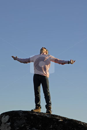 Pray stock photo, Young man with arms wide open and the sky as background by Rui Vale de Sousa