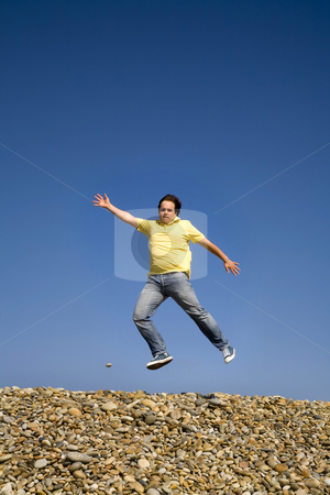 Jumping up stock photo, Young man jumps on beach, with the sky as background by Rui Vale de Sousa