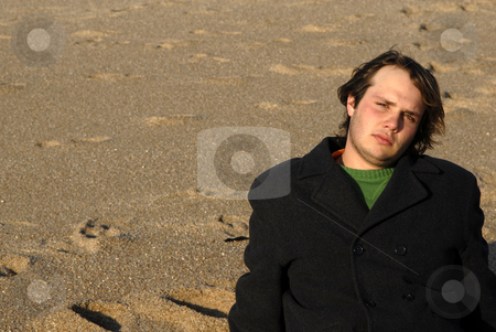 Man stock photo, Young man at the beach seated in the sand by Rui Vale de Sousa