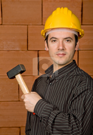 Worker stock photo, Man with yellow hat with a brick wall as background by Rui Vale de Sousa