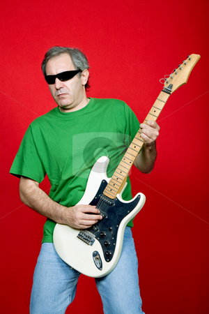Guitarist stock photo, Mature casual man plauing guitar on a red background by Rui Vale de Sousa