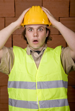 Worried stock photo, Foreman with yellow hat with a brick wall as background by Rui Vale de Sousa