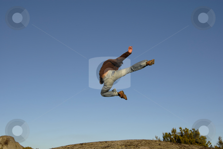 Jump kick stock photo, Young man jumps high in the mountain by Rui Vale de Sousa