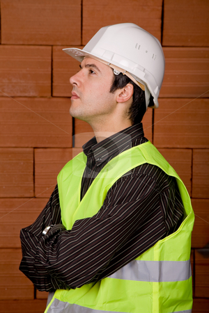 Pensive stock photo, Engineer with white hat with a brick wall as background by Rui Vale de Sousa