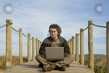 Worker stock photo, Young man working with computer at the beach by Rui Vale de Sousa