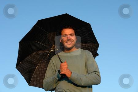 Umbrella stock photo, Young man with umbrella at sunset light by Rui Vale de Sousa