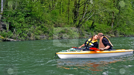 Young Couple Kiss While Kayaking stock photo, This sweet photo of romance shows a young Caucasian couple giving a kiss while on a mountain river kayaking. by Valerie Garner