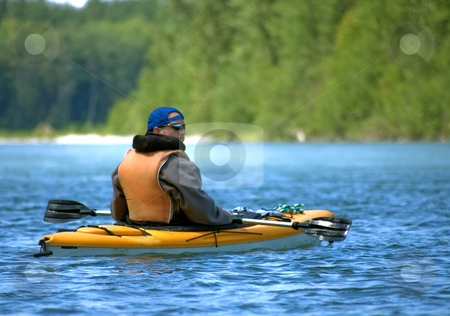 Young Male Canoeing in Beautiful River stock photo, Young adult man is enjoying a leisure water sport of canoeing in a beautiful mountain river. by Valerie Garner