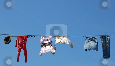 Clothes Line stock photo, Old clothes hanging on the line against blue sky. by Denis Radovanovic