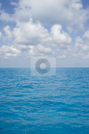 Bahama Surface Clouds Portrait stock photo, Portrait oriented background image of blue ocean water with a partly cloudy sky by A Cotton Photo