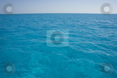 Bahama Surface Landscape stock photo, Landscape oriented background image of blue ocean water with a clear sky by A Cotton Photo