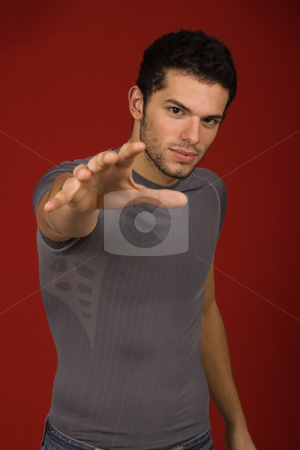 Reach stock photo, Portrait of sexy young man, against red background by Rui Vale de Sousa