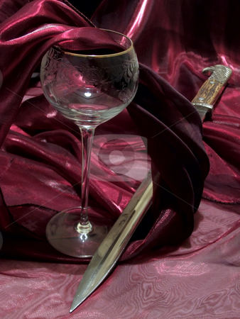 Wine and bayonet stock photo, Broken wineglass from crystal and bayonet among dark red tissue by Sergej Razvodovskij