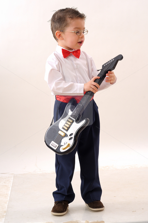 Small boy stock photo, Small boy playing to a guitar by Dragos Iliescu