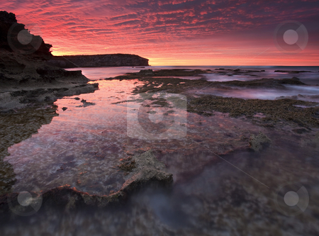 Red Sky At Morning stock photo, A spectacular sunrise over the tidepools at PEnnington Ba, South Australia. It lasted for a few moments before the gathering storm blotted out the light and the rains came. by Mike Dawson