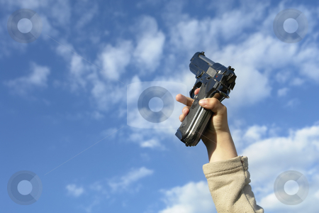 Gun stock photo, Gun in a child hand with clouds in the sky by Rui Vale de Sousa