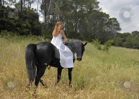 Bride and horse stock photo, Young woman in a wedding dress on a black stallion by Bonzami Emmanuelle