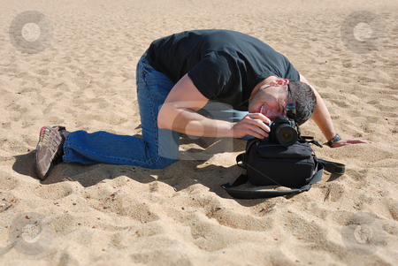 Photographer improvising stock photo, Photographer on the beach using a bag to place his camera. by Ivan Paunovic