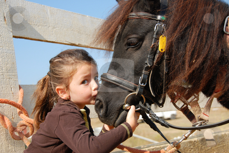 Little girl and her pony stock photo, Little girl kissing and her purebred shetland pony by Bonzami Emmanuelle