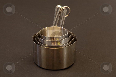 Measuring cups stock photo, Measuring cup is a kitchen utensil used primarily to measure the volume of liquid or powder-form cooking ingredients such as water, milk, juice, flour, and sugar by Mariusz Jurgielewicz