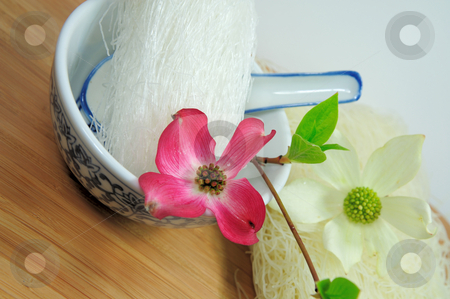 Rice And Mung Bean Noodles stock photo, Dried asin noodles in a blue and white ceramic oriental bowl with spoon on a bamboo cutting board topped with pink and white Dogwood flowers by Lynn Bendickson