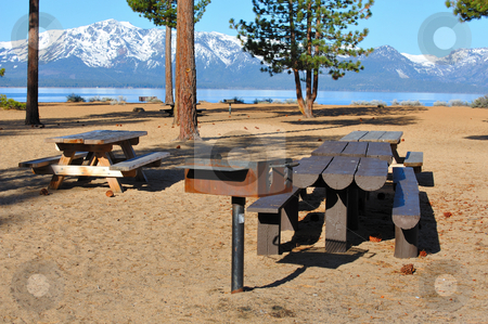 Lake Tahoe Picnic Area stock photo, Tables and barbecue on a sandy beach with pine trees looking across Lake Tahoe to the east side at early morning on a sunny day. by Lynn Bendickson