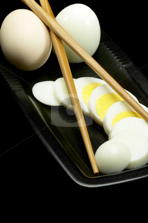Boiled eggs stock photo, Fresh boiled eggs one whole ,one peeled and another sliced on a black plate with chopstick by Francesco Perre
