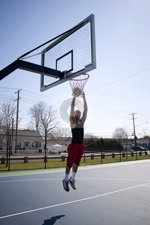 Man Dunking a Basketball stock photo, A young basketball player driving to the hoop. by Todd Arena