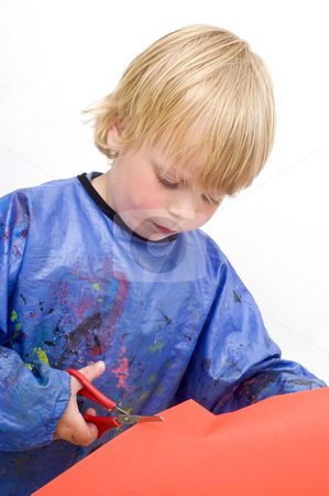 Cutting paper stock photo, Child cutting a sheet of red paper with a pair of scissors by Corepics VOF