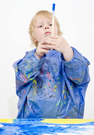 The Brush stock photo, Young boy holding a brush up straight above his head, as if worshipping it. Focus on brush and hands by Corepics VOF