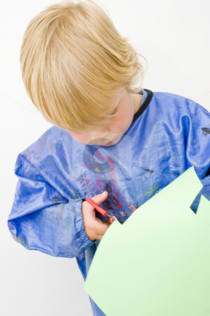 Cutting paper stock photo, Young child cutting a green sheet of paper with a pair of scissors by Corepics VOF