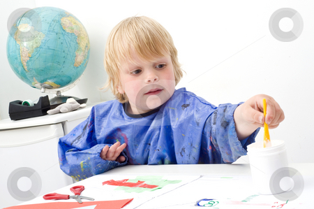 Reaching boy stock photo, Boy reaching for the jar of glue with a small brush by Corepics VOF