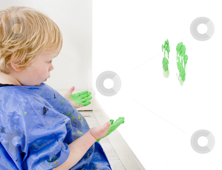 Scoundrel stock photo, A young boy examining his mischief - the green hand prints he just made on a wall by Corepics VOF