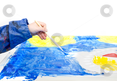 Poster painting stock photo, The hand of a young child holding a brush with blue poster paint by Corepics VOF