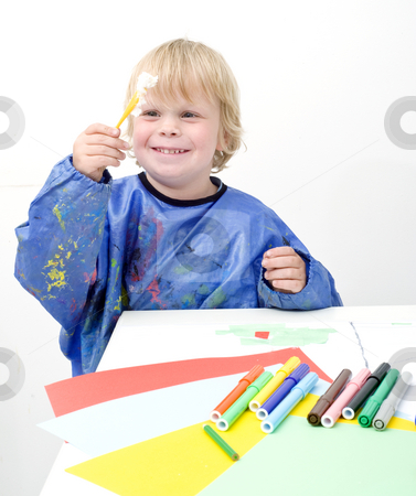 Messing with glue stock photo, Young boy holding up a small brush with glue by Corepics VOF